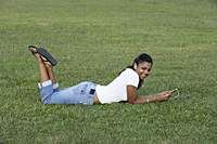 Young woman laying on grass listening to MP3 player - Asia Images Group