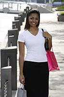 woman walking outside holding shopping bags outside - Asia Images Group