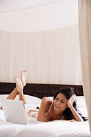 Indian woman laying on bed looking at laptop computer - Asia Images Group