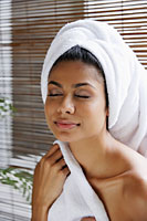 Indian woman closing her eyes relaxing with towel on her head - Asia Images Group