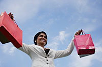 Indian woman smiling and holding up shopping bags. - Asia Images Group