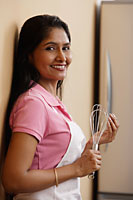 Indian woman smiling in the kitchen - Asia Images Group