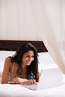 Indian woman laying on bed looking at laptop computer and smiling - Asia Images Group