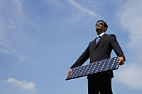Businessman holding solar panel. - Asia Images Group