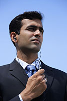 Indian businessman using handsfree device. - Asia Images Group