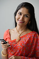 Indian woman wearing a sari and using a mobile phone - Asia Images Group