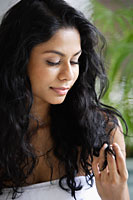 Indian woman looking at her hair - Asia Images Group
