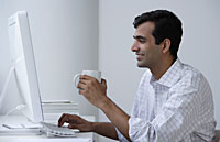 Indian man working on computer and drinking coffee - Asia Images Group