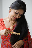 Indian woman wearing a sari and combing her hair - Asia Images Group