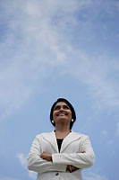 Indian woman smiling and looking up with blue sky background - Asia Images Group