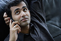 Indian businessman looking up while talking on phone. - Asia Images Group