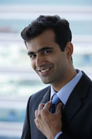 Head shot of Indian businessman smiling. - Asia Images Group