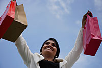 Indian woman smiling and holding up shopping bags - Asia Images Group