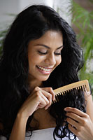 Indian woman smiling and combing her hair. - Asia Images Group