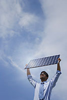Businessman holding solar panel outside. - Asia Images Group