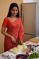Indian woman wearing a sari while making dinner in the kitchen - Asia Images Group