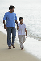 Father and son holding hands and walking down the beach. - Asia Images Group