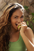 Young woman biting green apple - Asia Images Group