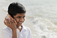 Young boy listening to sea shell - Asia Images Group