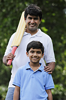 Father holding cricket bat with son - Asia Images Group