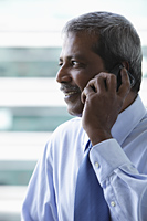 Head shot of mature Indian business man talking on phone - Asia Images Group