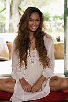 Young woman with long hair sitting on floor smiling - Asia Images Group