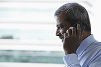 Head shot of mature Indian man talking on phone - Asia Images Group