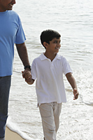 Father holding son's hand while walking on beach - Asia Images Group