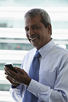 Head shot of mature Indian man holding hand phone - Asia Images Group