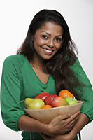 Woman wearing green top holding bowl of fruit - Asia Images Group