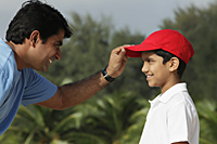 Father putting on son's baseball cap. - Asia Images Group