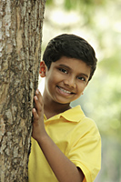 Young boy peeking out from behind a tree - Asia Images Group