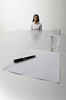 Young woman sits at end of the table waiting to be interviewed - Asia Images Group