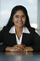 Indian business woman sitting at desk with hands folded - Asia Images Group