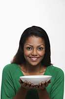 Young woman holding white bowl and smiling - Asia Images Group