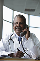 Indian doctor talking on phone and smiling - Asia Images Group