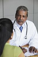 Indian doctor talking to patient - Asia Images Group