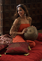 Young woman sitting on pillows holding Indian antiques - Asia Images Group