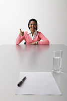 Young woman sitting at table during interview giving thumbs up sign - Asia Images Group