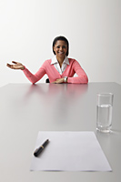 Young woman sitting at end of table being interviewed - Asia Images Group