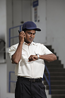 Security guard looking at watch and talking on phone - Asia Images Group