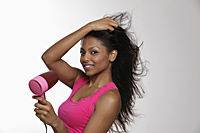 woman blow drying her long hair and smiling - Asia Images Group