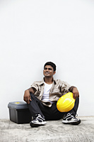 Man sitting on ground holding construction hat - Asia Images Group