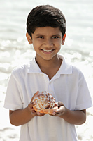 Young boy holding sea shell and smiling - Asia Images Group