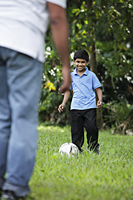Young boy kicking ball to his father - Asia Images Group