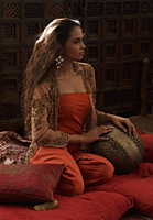 Young woman relaxing on pillows with Indian antiques - Asia Images Group