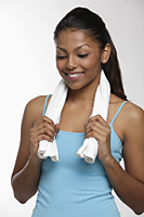 Woman holding towel around neck and smiling - Asia Images Group