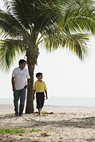 Father and son walking along the sea - Asia Images Group