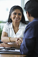 Indian woman shaking hands with male colleague - Asia Images Group