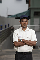 Security guard standing with arms folded - Asia Images Group